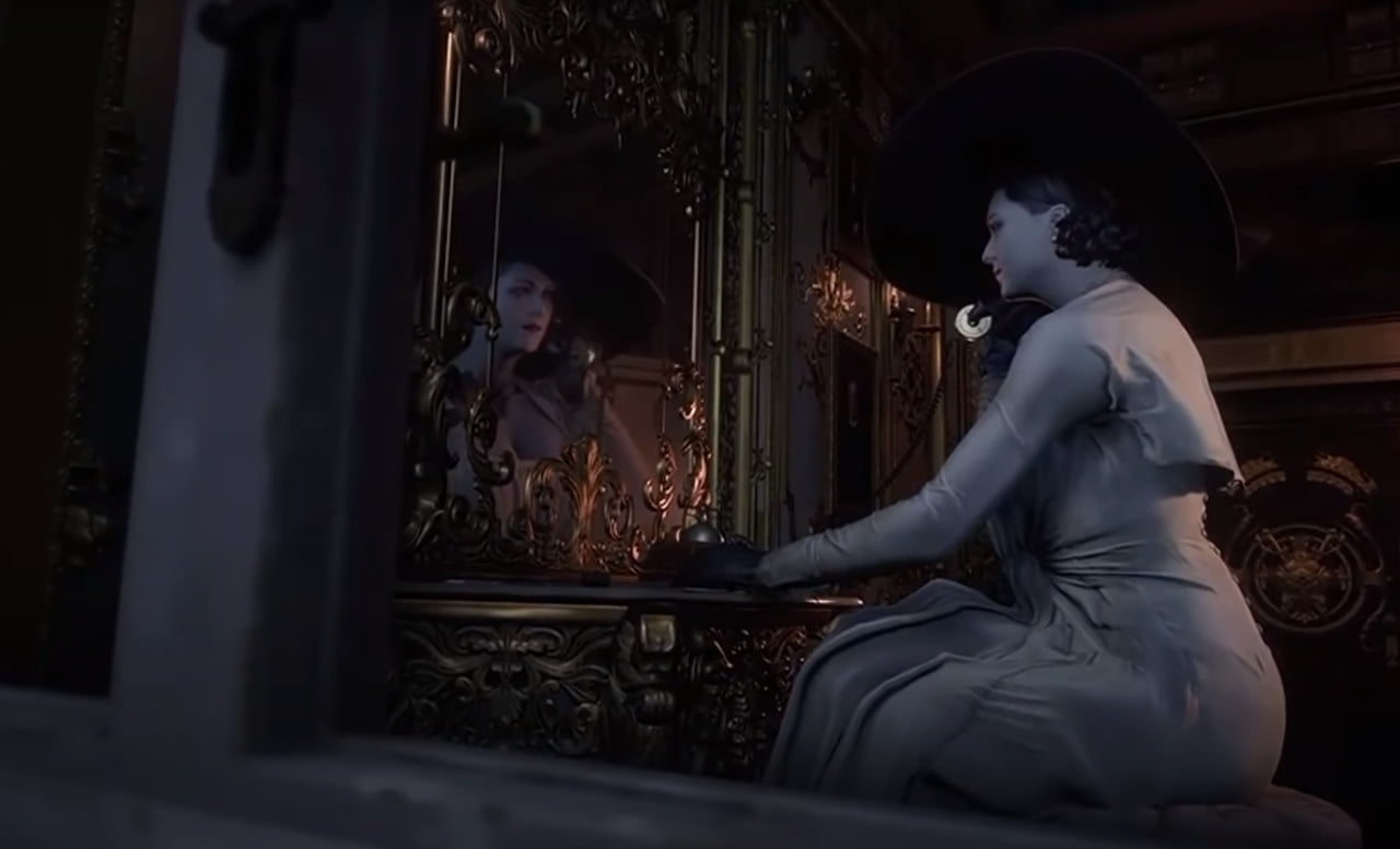 Alcina Dimitrescu sits in front of a mirror