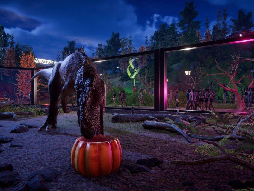 A dinosaur eats from a Halloween pumpkin in Prehistoric Kingdom